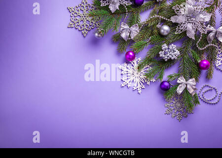 Purple Christmas and New Year background with decorated fir tree and toys. Space - Stock Photo