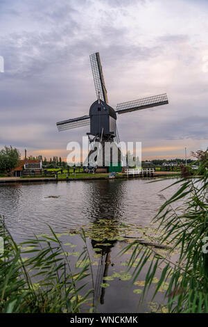Majestic windmill reflected on the calm canal water during the bleu hour sunset in Alblasserdam city, Netherlands - Stock Photo