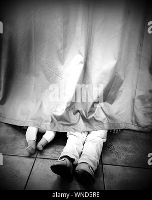 Low Section Of Parent And Child Hiding Behind Curtain - Stock Photo