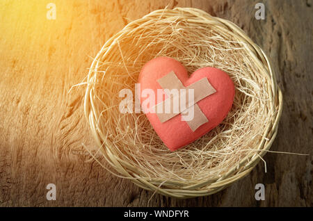 High Angle View Of Bandages On Red Heart Shape Food In Nest At Table - Stock Photo