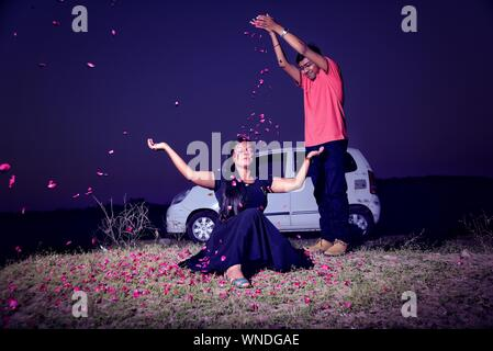 Man Showering Flowers On Woman Sitting Outdoors Against Sky At Night - Stock Photo