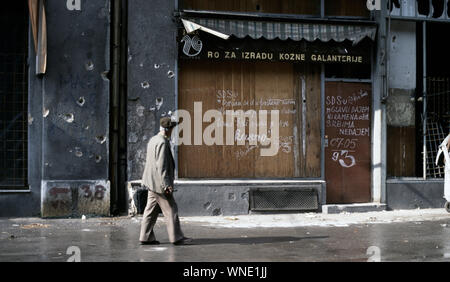 18th May 1993 During the Siege of Sarajevo: anti-Serb graffiti written on a boarded-up shop front on Maršala Tita Street in the city centre. It is addressed to Radovan Karadžić's SDS (Serb Democratic Party). - Stock Photo