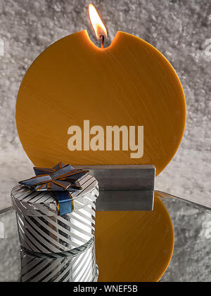 Close-up Of Presents And Candle On Snow - Stock Photo