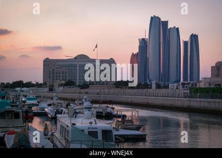Beautiful view of Abu Dhabi city Etihad towers, famous landscape and Marina boats - Stock Photo