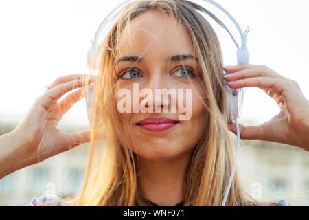 Beautiful young blonde woman with long hair and blue eyes listening to music with white headpones outside. Hands on headphones. Rome, Italy, Sunset. Stock Photo