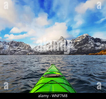 Small green kayak in bay fjord in the Lofoten Islands surrounded with snowy mountains and blue sky. Norway