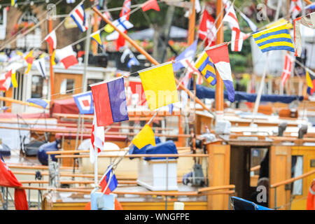 St. Katharine Docks, London, 06th Sep 2019. Vessels are decorated with colourful flags. Classic boats and barges, including the Royal barge Gloriana, decorated smaller vessels and water craft are moored in St. Katharine Docks for the annual Classic Boat Festival. The free festival also features food and drink stalls, stages, bands and free paddle boarding and other activities, and is on for three days until Sunday 8th September. Credit: Imageplotter/Alamy Live News Credit: Imageplotter/Alamy Live News - Stock Photo