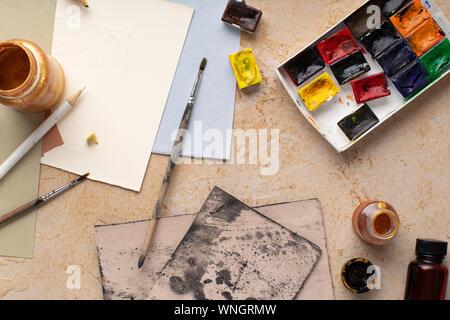 Artist's workspace flatlay. Art equipment on rustic background. Overhead image. - Stock Photo