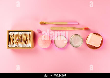Plastic-free, zero waste cosmetics, flat lay on a pink background. Bamboo toothbrushes and cotton swabs, konjac sponge, natural organic products - Stock Photo