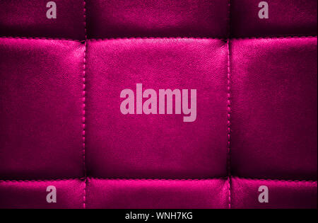 Shiny electric pink artificial textured leather stitched with thread. Close-up of sofa surface. View from directly above. Highly detailed background w - Stock Photo