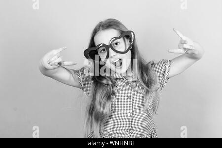 Power of love. Kid girl heart shaped eyeglasses. Girl adorable smiling face fall in love. Child charming smile blue background. Kid happy lovely enjoy childhood. Heart symbol of love. Fashion eyewear. - Stock Photo