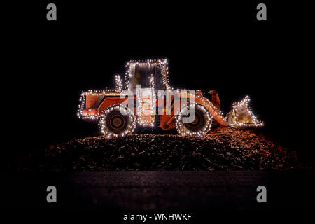 Blurred wheel loader decorated with lights at christmas - Stock Photo