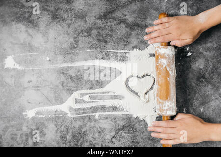 Baking background. Girl hands keep rolling pin and heart of flour on gray table with copy space, top view. Valentine's Day - Stock Photo