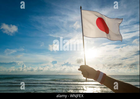 Hand with red and white Team Japan wristband holding a Japanese flag waving in front of golden sunrise scene at the beach - Stock Photo