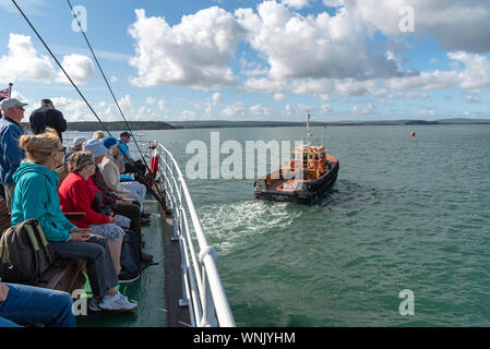 Poole Harbour, Dorset, England, UK. September 2019. Tug assiting SS Shieldhall from the berth watched by passengers seated on the stern - Stock Photo