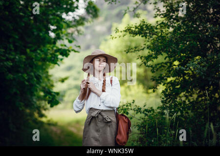 Lovely young woman with red hair, in a hat and with a backpack on the edge of the forest. Beautiful red-haired girl on a walk - Stock Photo