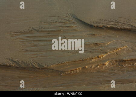 Delicate lines in the sands of a beach where the fresh water emerging from a spring has washed away a layer of sand leaving a patterned area. - Stock Photo