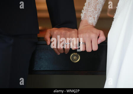 Cropped Hands Of Newlywed Couple Showing Wedding Rings At Table - Stock Photo