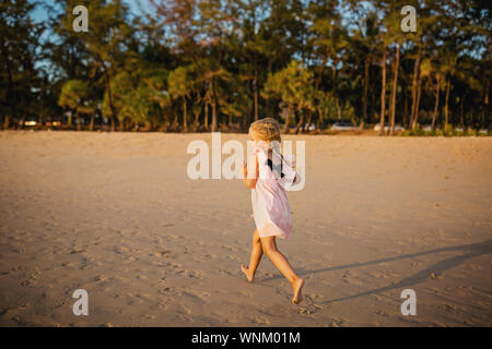 Cute little girl running on the beach. Sunset time. Kid having fun in holiday vacation with back sun light - Youth, lifestyle, travel and happiness - Stock Photo