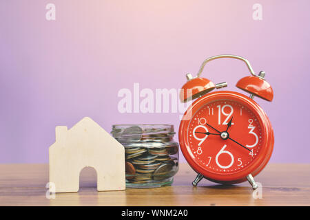 Alarm Clock By Coins In Container With Model House On Wooden Table Against Wall - Stock Photo