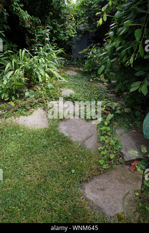 Path made of split stones laid in the garden lawn - Stock Photo