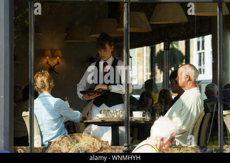 Waitress serving a couple at a table in Bettys Tea Rooms,Harrogate,North Yorkshire,England. - Stock Photo