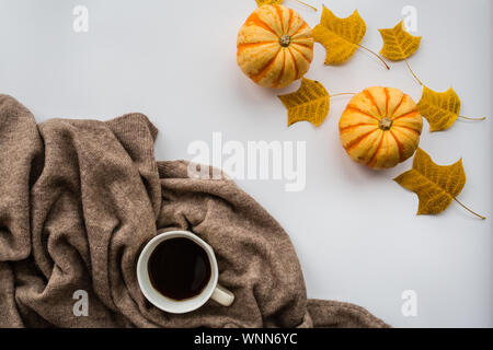 Thanksgiving holiday objects for mock up template design. Autumn pumpkin, black coffee cup, knitted sweater and fall leaves. View from above. Flat lay - Stock Photo