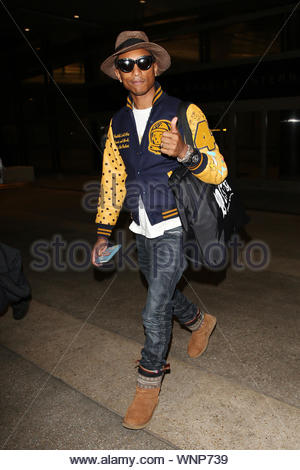 Los Angeles, CA - Pharrell Williams arrives in Los Angeles at LAX with wife Helen Lasichanh. The singer-songwriter, rapper, record producer, musician, and fashion designer gave the thumbs up when asked about his flight. AKM-GSI May 28, 2014 - Stock Photo
