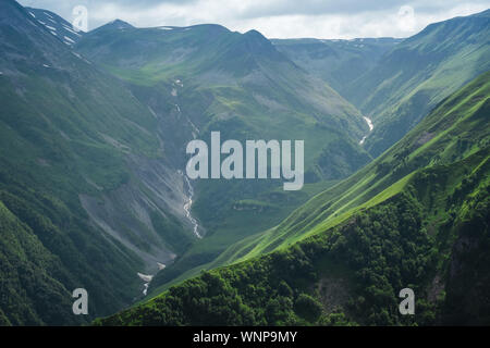 Caucasian Mountain ranges and valleys at Gudauri, Georgia. Summer day on the military-Georgian road. Rapid weather change in the mountains - Stock Photo