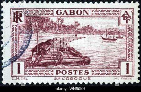 Log raft on old postage stamp of Gabon - Stock Photo