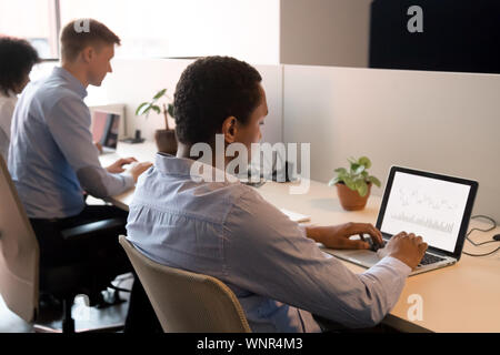 Focused black analyst working on laptop in coworking space - Stock Photo