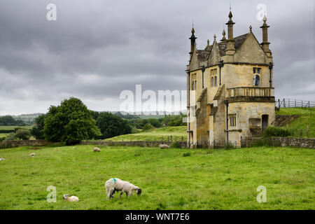 Sheep grazing in field at 17th Century East Banqueting Hall beside St James' church under cloudy sky in Chipping Campden England - Stock Photo