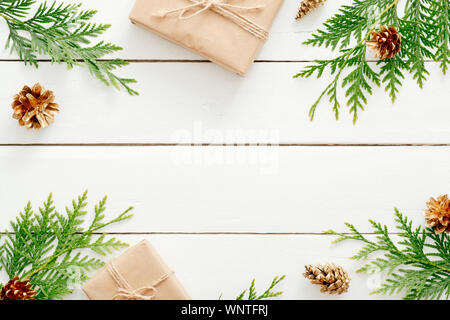 Christmas composition. Christmas fir tree branches, gifts, pine cones on wooden white rustic background. Flat lay, top view. Copy space. Banner mockup - Stock Photo