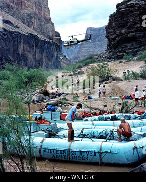 Helicopters descend between canyon walls with adventure travelers who join other passengers waiting to board two large neoprene rafts for a float trip down the Colorado River that runs through Grand Canyon National Park in Arizona, USA. Each of the outboard motor-powered boats carries up to 14 passengers and two crew members, plus food and camping supplies for 3-1/2 to 8-day outings that wind from 88 to 188 miles (142 to 303 kilometers) through the famous river canyon. The longer the trip, the more thrills through water-splashing rapids along the way; life jackets are provided. Transportation - Stock Photo