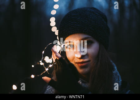 Close up portrait of beautiful young woman holding Christmas lights