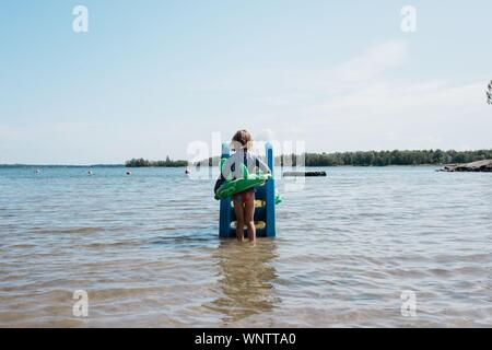 girl with inflatable on playing on a slide in the sea in summer