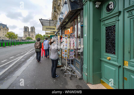 A tourist searches for postcards in Paris, France, at a sidewalk souvenir shop on the banks of the Seine River with the Notre Dame Cathedral in view - Stock Photo