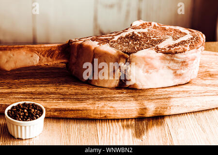 Dry aged raw tomahawk beef steak on wooden board and pepper - Stock Photo