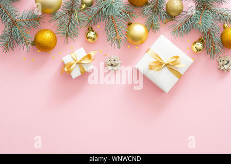 Christmas frame border with fir tree branches, Christmas golden balls, presents on pastel pink background. Flat lay, top view. - Stock Photo