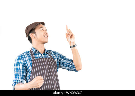 The young asian man who is wearing an apron confidently smile and point to something above him isolated on white background. Portrait man with copy sp - Stock Photo