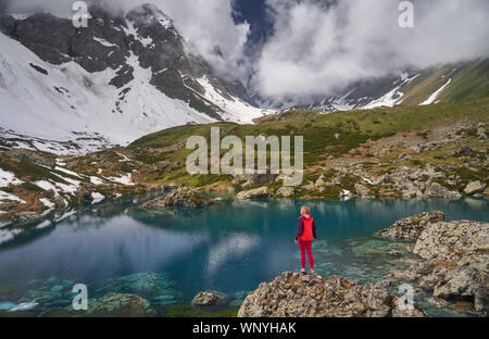 Hiking woman in red jacket stay at beautiful lake in mountains. - Stock Photo