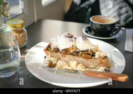 Breakfast with poached eggs and toast bread in a cafe - Stock Photo