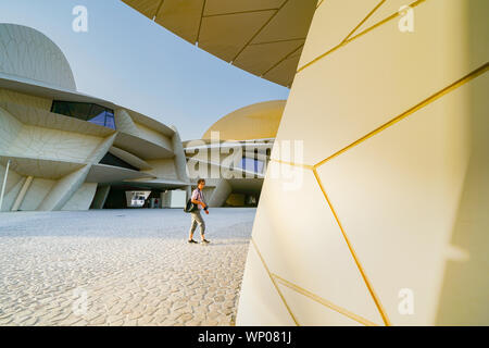 DOHA QATAR - JULY 10 2019; Tourist crosses courtyard in National Museum of Qatar unusual but striking design form is inspired by desert rose crystal o - Stock Photo