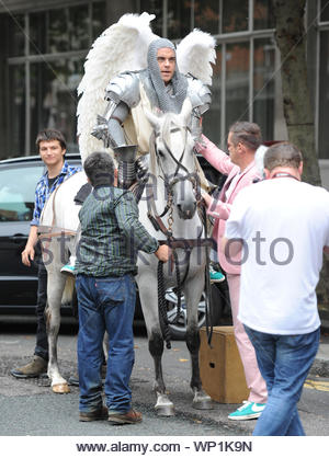 London, UK - Singer Robbie Williams gets back at it and continues filming his new music video in East London with Kaya Scodelario. Robbie was outfitted in full body armor with angel wings and riding a white horse. AKM-GSI August 17, 2012 - Stock Photo