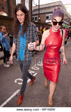 London, UK - Kelly Osbourne and her boyfriend Matthew Mosshart visit the House of Holland catwalk show at the Brewer Street Car Park in London as they walk hand in hand while Kelly chats away on her cell phone. AKM-GSI September 15, 2012 - Stock Photo