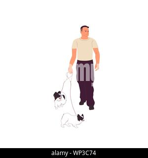 Young man in casual outfit is walking with two small papillon dogs on a leash. - Stock Photo