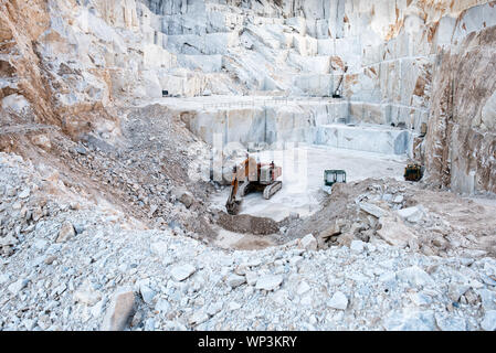 Excavator or digger inside an open cast mining pit for white Carrara marble showing large blocks of stone cut from the mountainside in Tuscany, Italy - Stock Photo