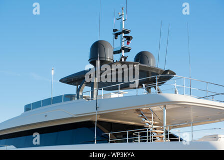 Radar and navigation equipment on the roof of a luxury white motor yacht against blue sky - Stock Photo