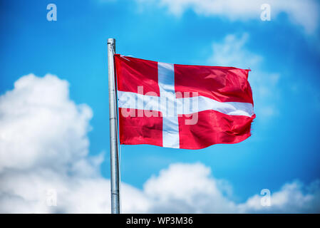 National flag of Denmark fluttering in the wind on a flagpole against a sunny blue sky with fluffy white cloud - Stock Photo