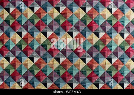 Geometric multicolored textile background pattern in a full frame view of diamond or square shapes with color shading - Stock Photo